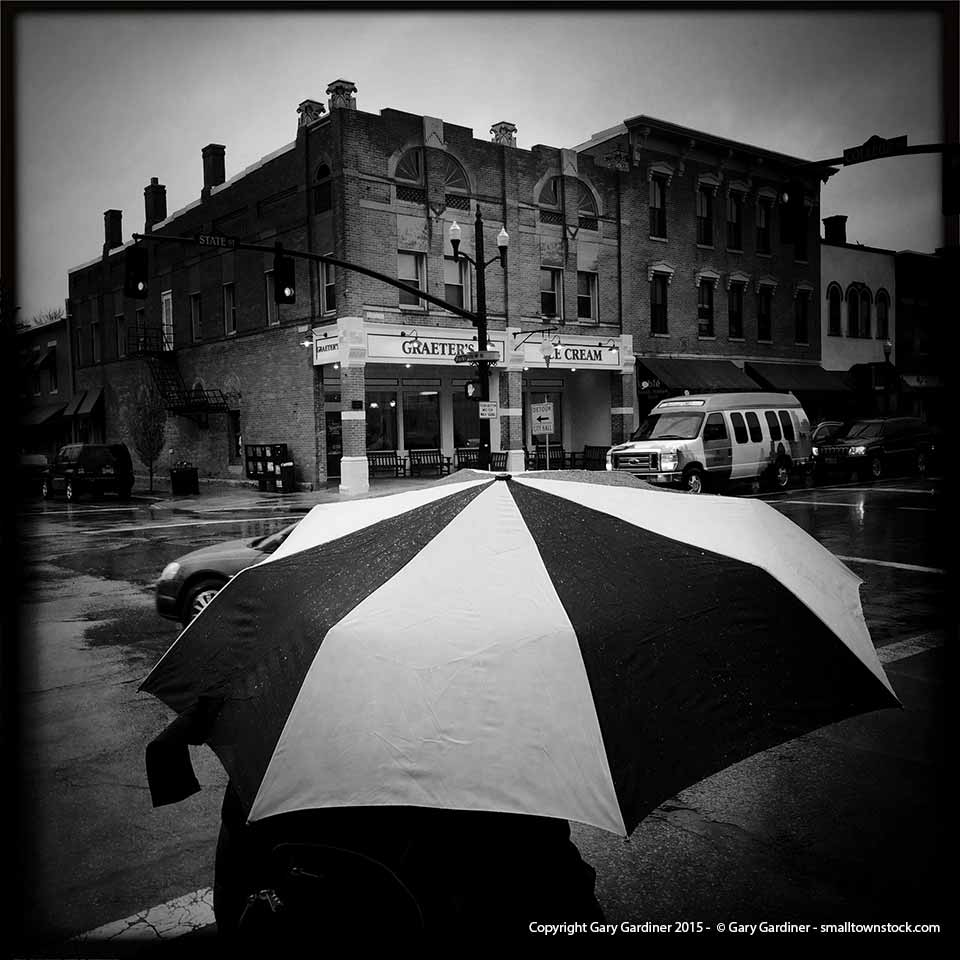A shopper shields himself from a day long rain storm as he waits to cross the street in Uptown Westerville. My Final Photo for March 13, 2015.