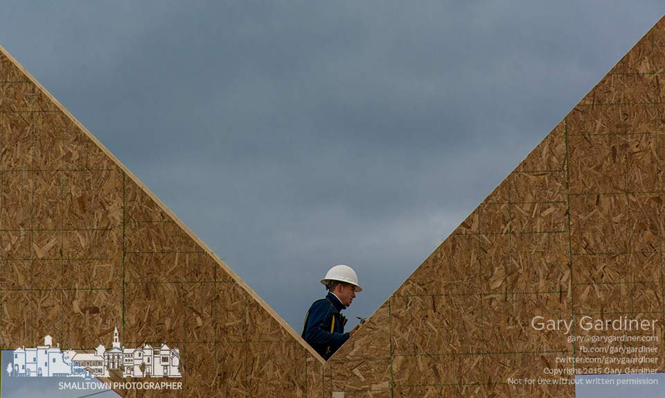 A carpenter stands at the center of two building panels for the clubhouse of an apartment complex under construction at The Ravines at Westar along Polaris Parkway. My Final Photo for April 22, 2015.