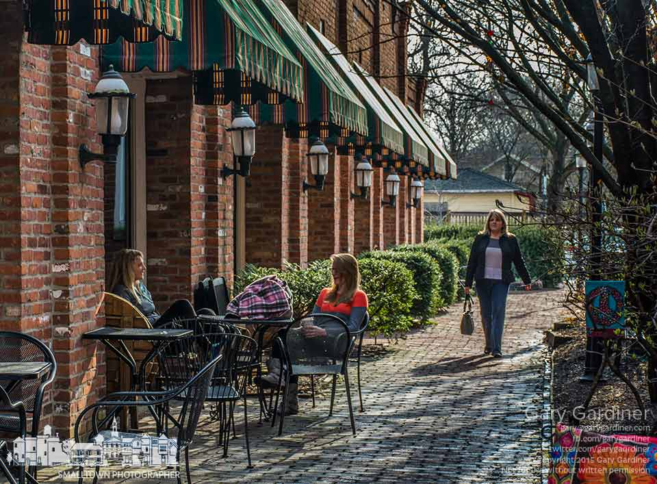 A woman walks along the brick pathway beside Java Central on a warm spring morning offering an open space for others to enjoy more pleasant weather than the recent winter record low temperatures. My Final Photo for April 9, 2015.