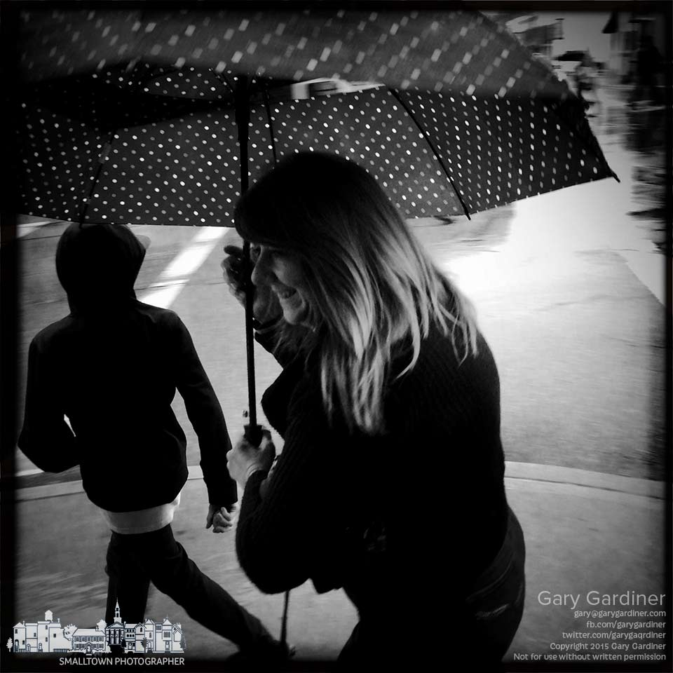 A woman and her son navigate their way around a street corner to get out of a late afternoon rainstorm. My Final Photo for April 3, 2015.