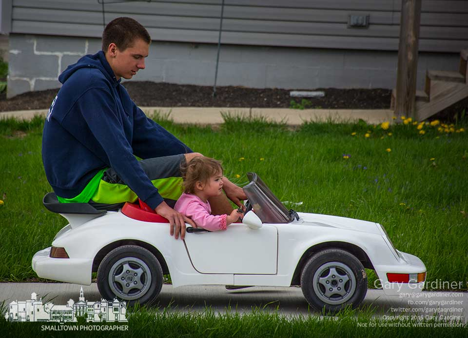 Sixteen-year-old Erics helps 18-month-old Logan steer the electric Porsche in a straight line along the sidewalk in front of his house as they enjoy a brisk spring ride in the neighborhood. My Final Photo for April 21, 2015.