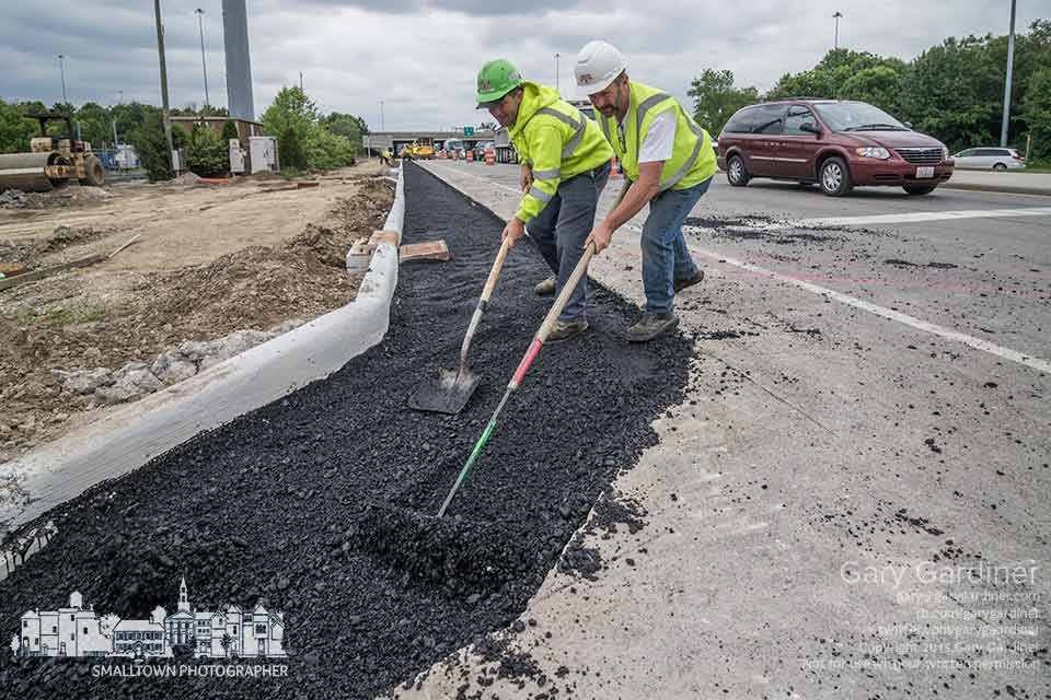 Two men using a rake and shovel move hot asphalt into a corner turn as part of the expansion of 3C Highway to make a wider roadway and add a bike path connecting Westerville to Blendon Township. My Final Photo for May 21, 2015.