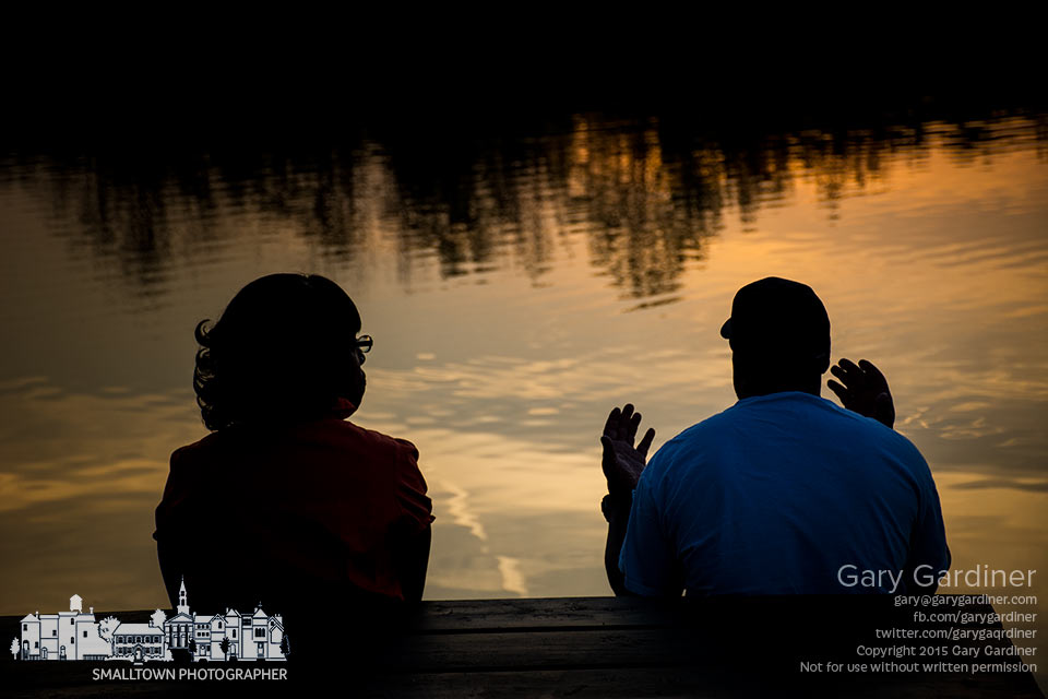 A couple enjoy the warm sunset of the lake at Sharon Woods Park where they settled on one of the benches for a late day talk. My Final Photo for May 5, 2015.