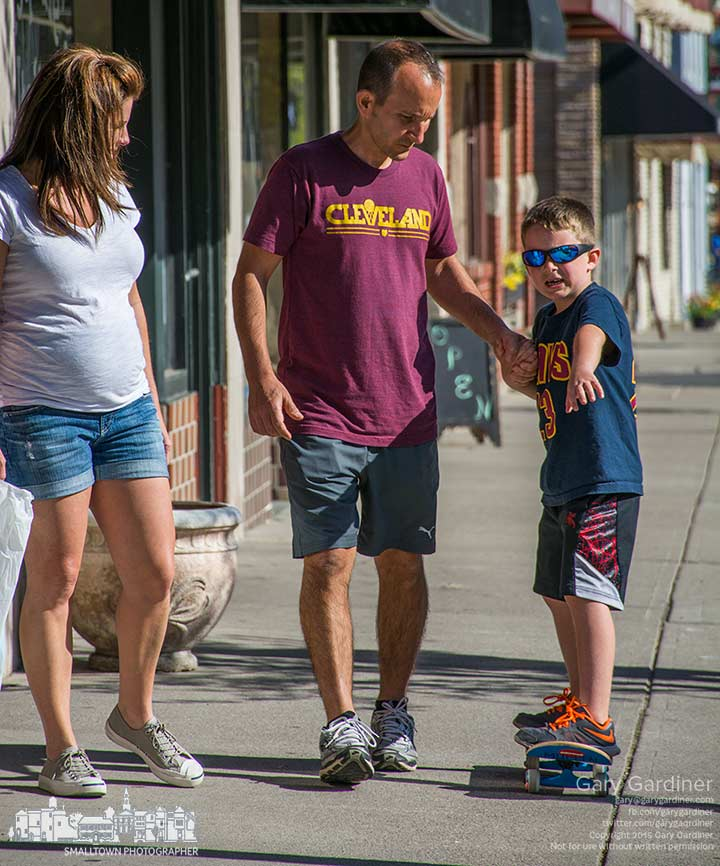 A father helps his son navigate his way along the sidewalk in Uptown after buying a new skateboard for the youngster. My Final Photo for May 1, 2015.
