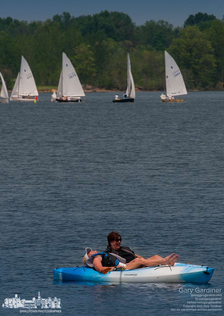Two women share a laugh while floating on their kayaks near the docks at the Hoover Sailing Club as its members run a race on Hoover Reservoir. My Final Photo for May 9, 2015.