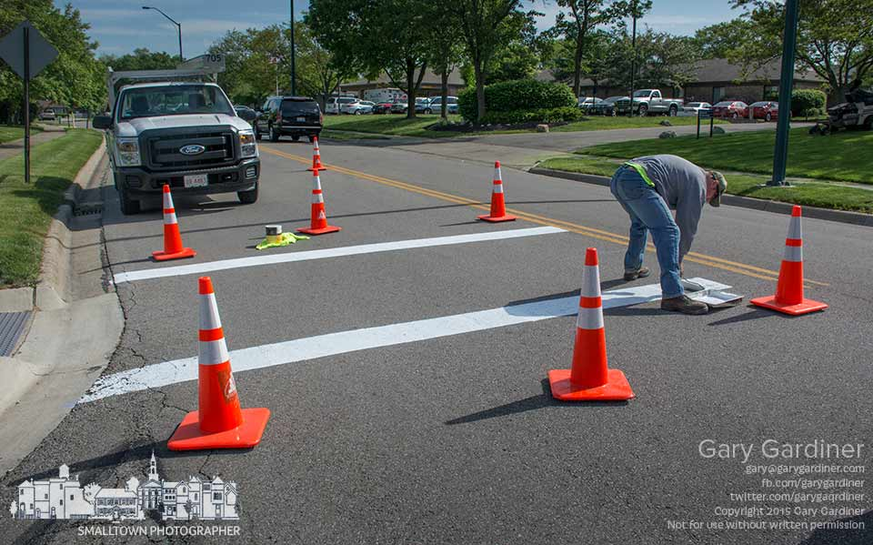 City workers use a paint roller to create a pedestrian crossing at the senior medical center on Eastwind Drive instead of the powered and heated paint machine used for larger and more complicated jobs. My Final Photo for May 14, 2015.