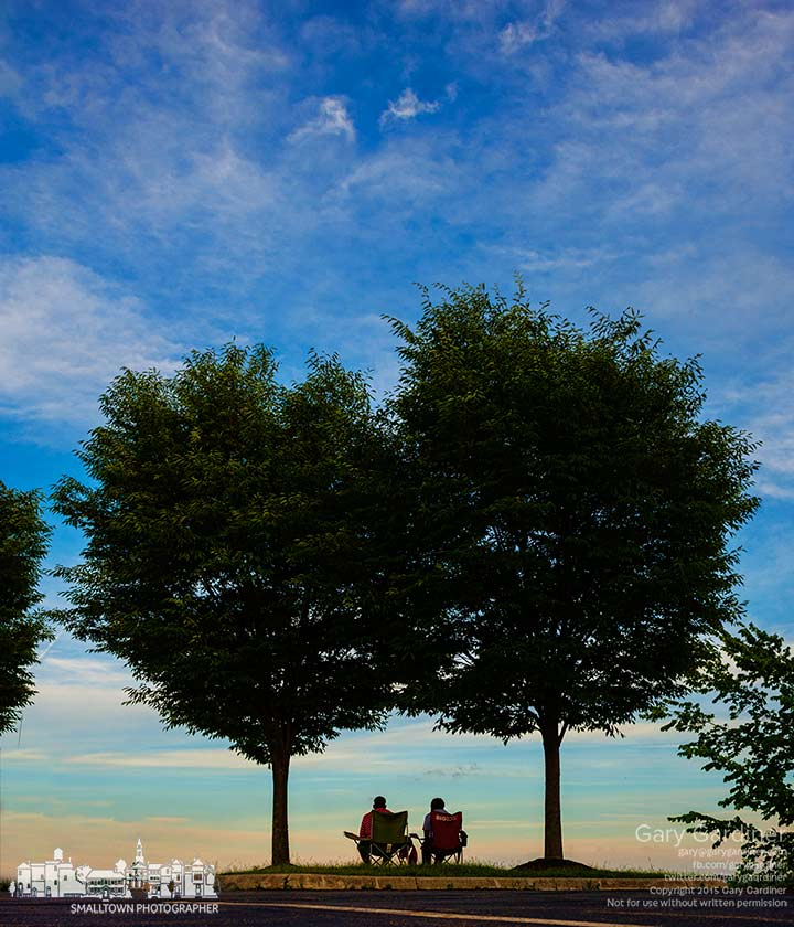 A couple sits under a pair of trees at sunset near a parking lot overlooking the shoreline of Hoover Reservoir. My Final Photo for June 21, 2015.