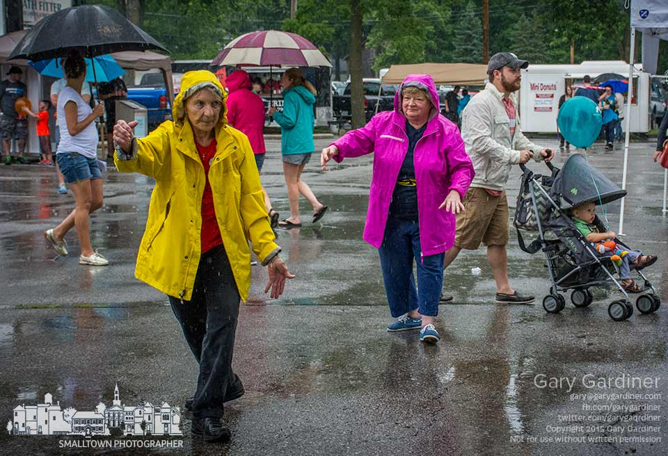 A pair of women perform Tai Chi inn the rain as a small crowd uses umbrellas to shield themselves from the rains at Fourth Friday in Uptown Westerville. My Final Photo for June 26, 2015.