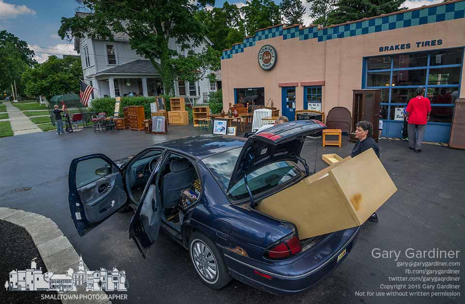 A woman loads a chest of drawers in her car's trunk and back seat after buying it from a garage sale in the front driveway of an auto repair shop in Uptown Westerville. My Final Photo for June 6, 2015.