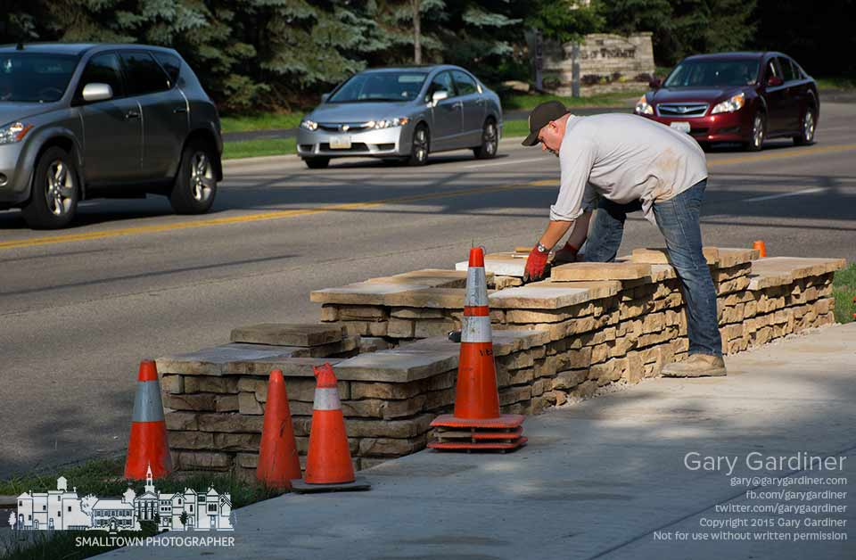A city worker places a stone on the top of one of two planters built on the berm along the sidewall beneath the bike and walk path bridge over County Line road. My Final Photo for June 11, 2015.
