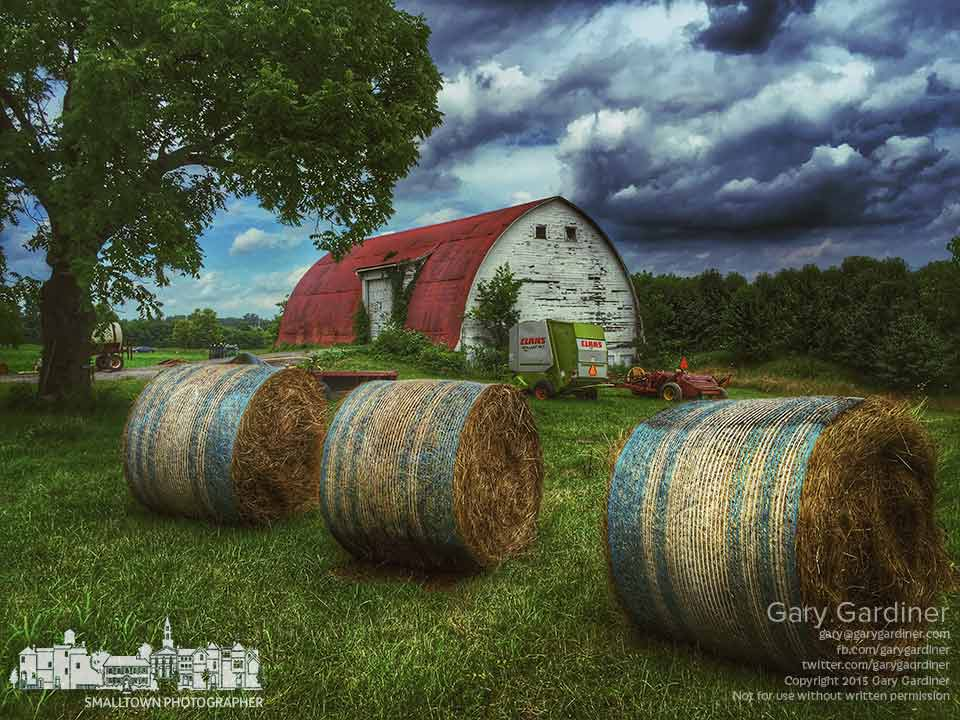 Three rolled bales of hay sit outside the barn with the baler and hay rake at the Braun Farm at Cooper Rd. and Cleveland Ave. My Final Photo for July 20, 2015.