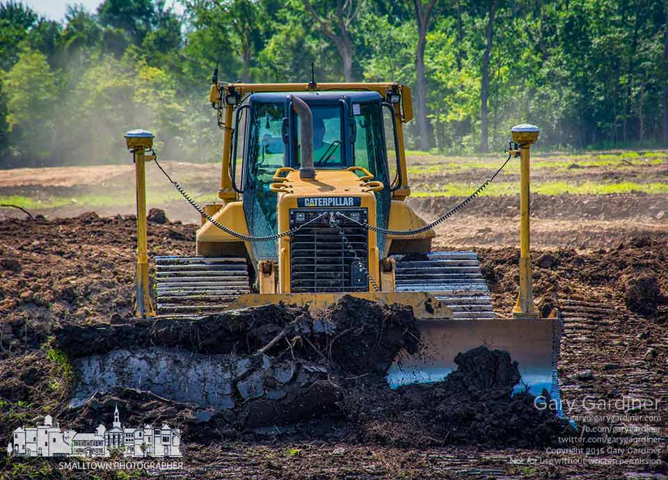 A pair of GPS receivers help guide a bulldozer and other earthmoving equipment as construction begins on an apartment complex on North State Street in Westerville. My Final Photo for July 23, 2015.