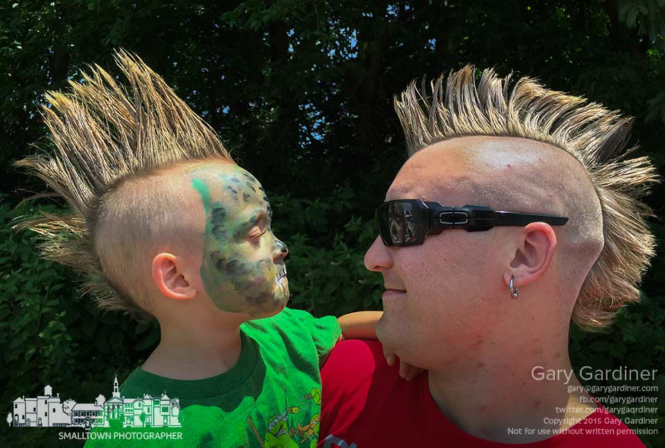 Father and son share Mohawk haircuts while the son separates himself by wearing zombie makeup as they enter the Westerville Music and Arts Festival. My Final Photo for July 11, 2015.
