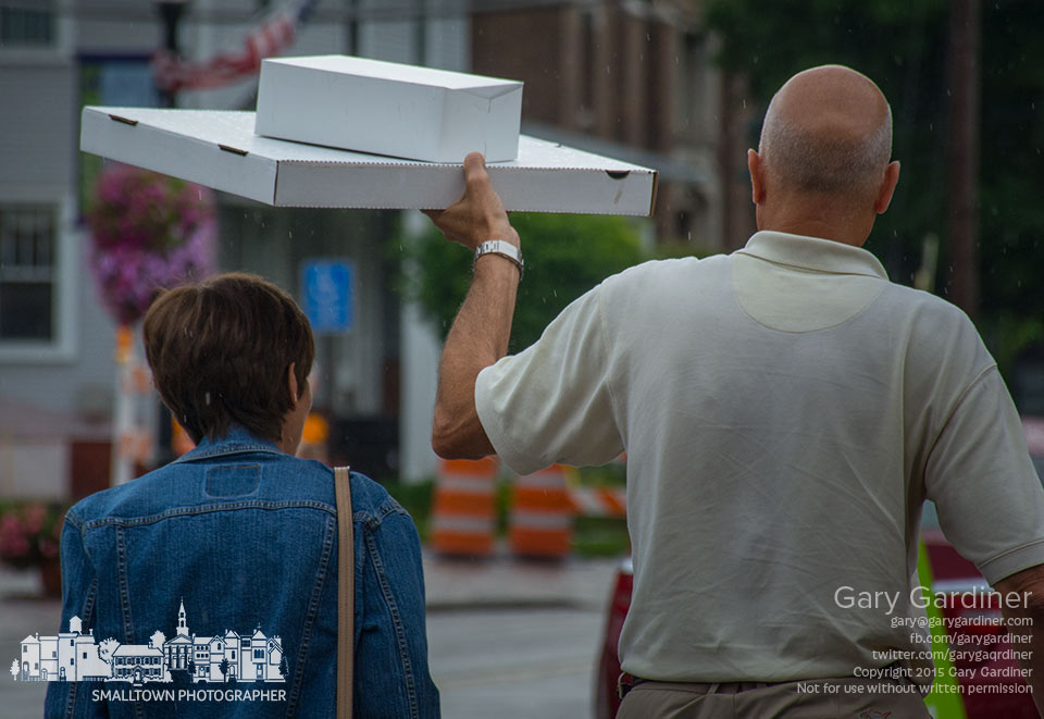 A man uses a pizza box to shield his wife from rain as they cross the street in uptown Westerville during a light drizzle in early evening. My Final Photo for July 10, 2015.