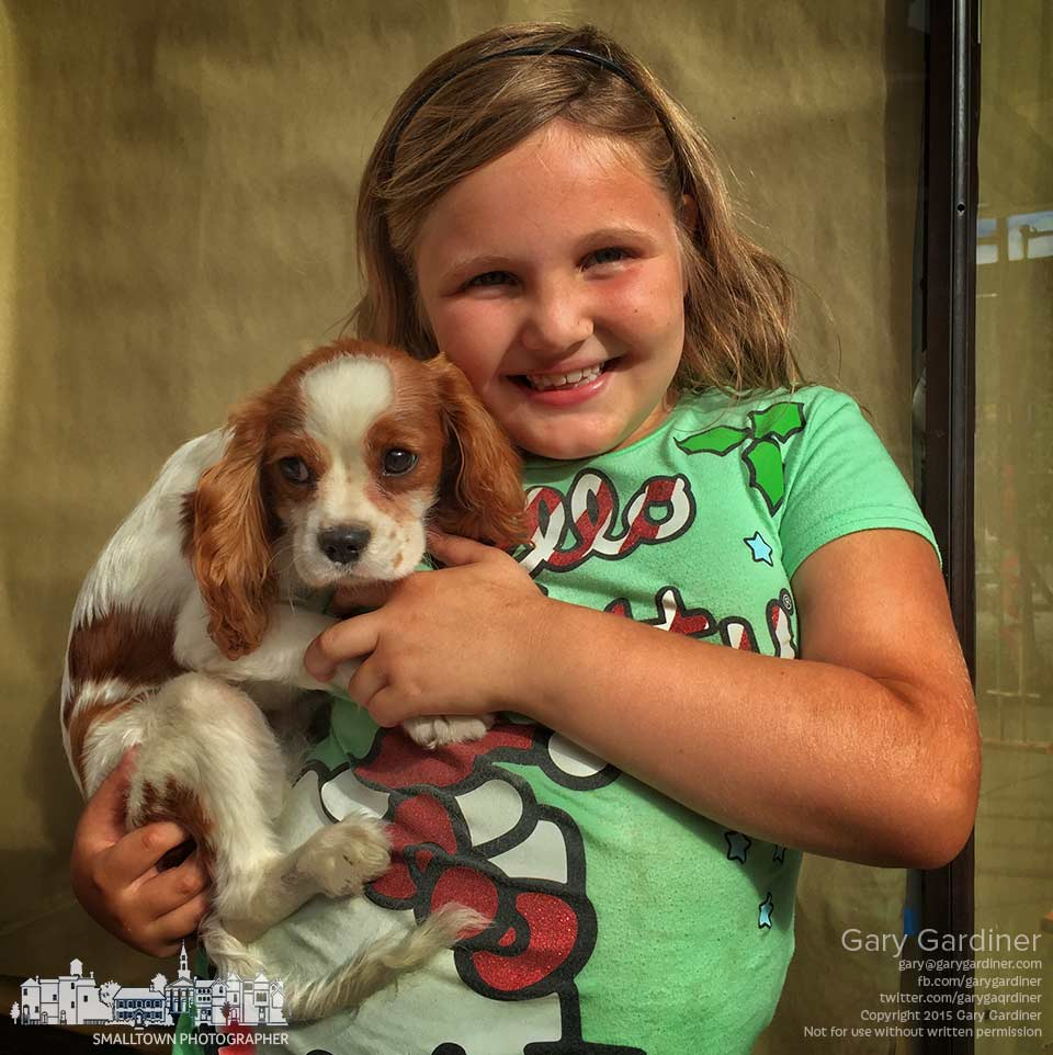 A young girl proudly poses with her puppy while walking with her family in Uptown Westerville. My Final Photo for July 16, 2015.
