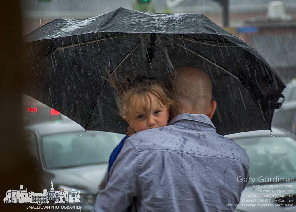 A child held tight with one hand is carried by her father while the other hand shares an umbrella against blowing rain in Uptown Westerville, My Final Photo for July 7, 2015.
