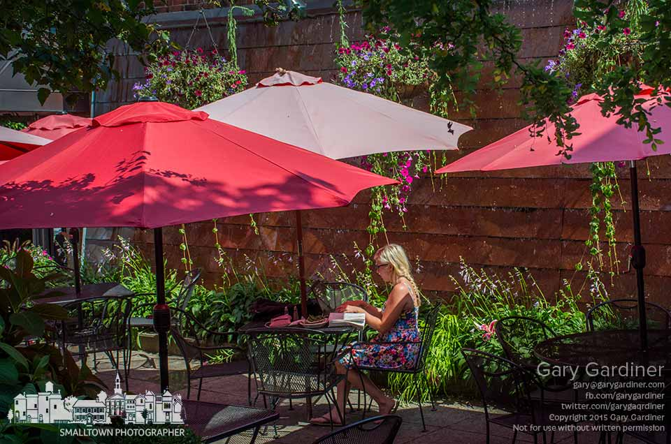 A woman works on her computer on the patio of Jimmy V's on a warm summer afternoon while waiting for a friend to arrive in Uptown. My Final Photo for July 25, 2015.