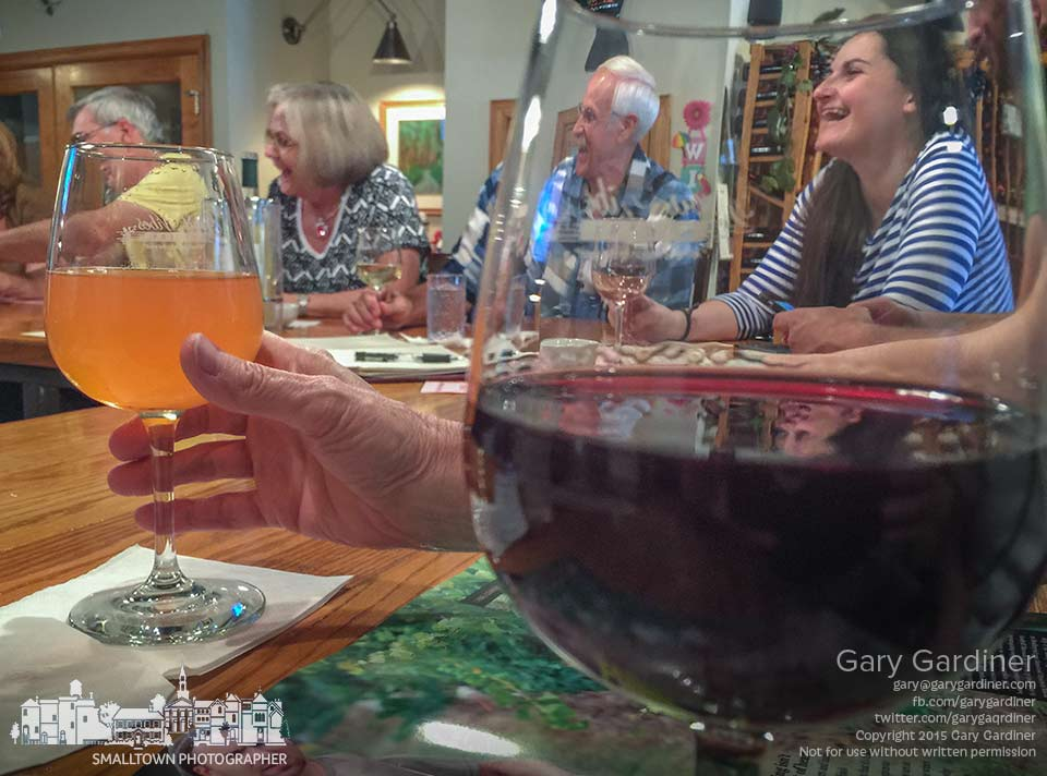 Customers laugh and enjoy special pricing during the third anniversary Friday night for Good Vibes Winery in Uptown Westerville. My Final Photo for July 17, 2015.