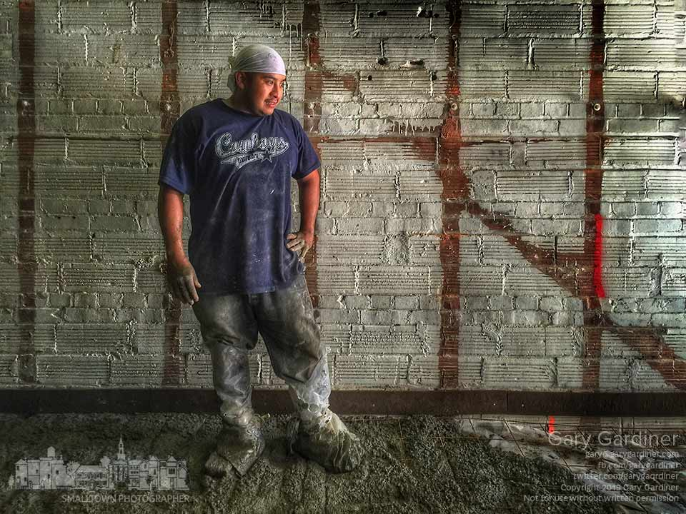 A construction worker pouring concrete for the kitchen at 8 State Bistro wears duct-taped plastic to protect his shoes after failing to bring his work boots to the job. My Final Photo for Aug. 21, 2015.
