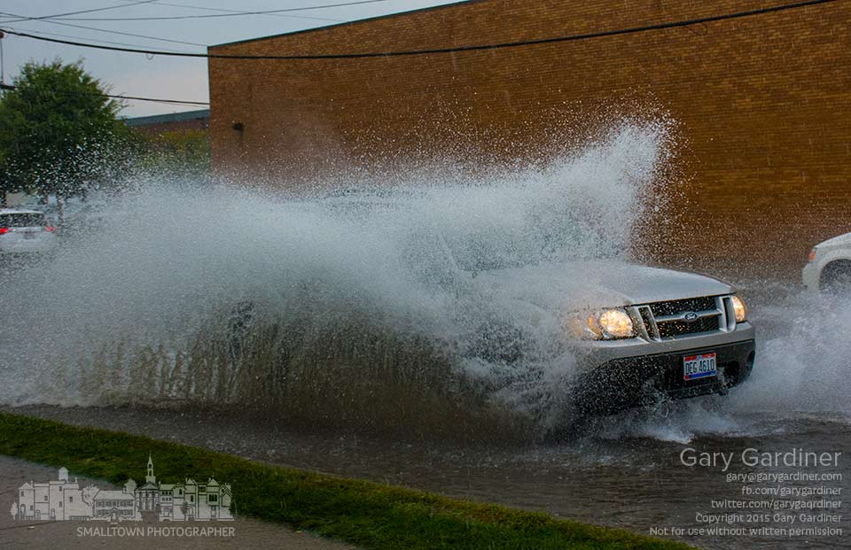 An SUV splashes water over its height as it travels through water flooding a short section of Schrock Road in front of Kroger during a heavy rain squall. My Final Photo for Aug. 31, 2015.