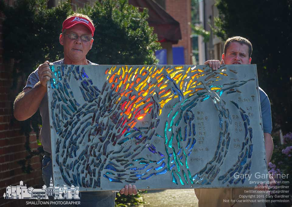 Owners of one of the Dr. Foltz windows removed from Pasquale's restaurant in Uptown Westerville carries a section of the glass artwork to their pickup truck as demolition begins inside the building for Asterisk Supper Club. My Final Photo for Aug. 13, 2015.