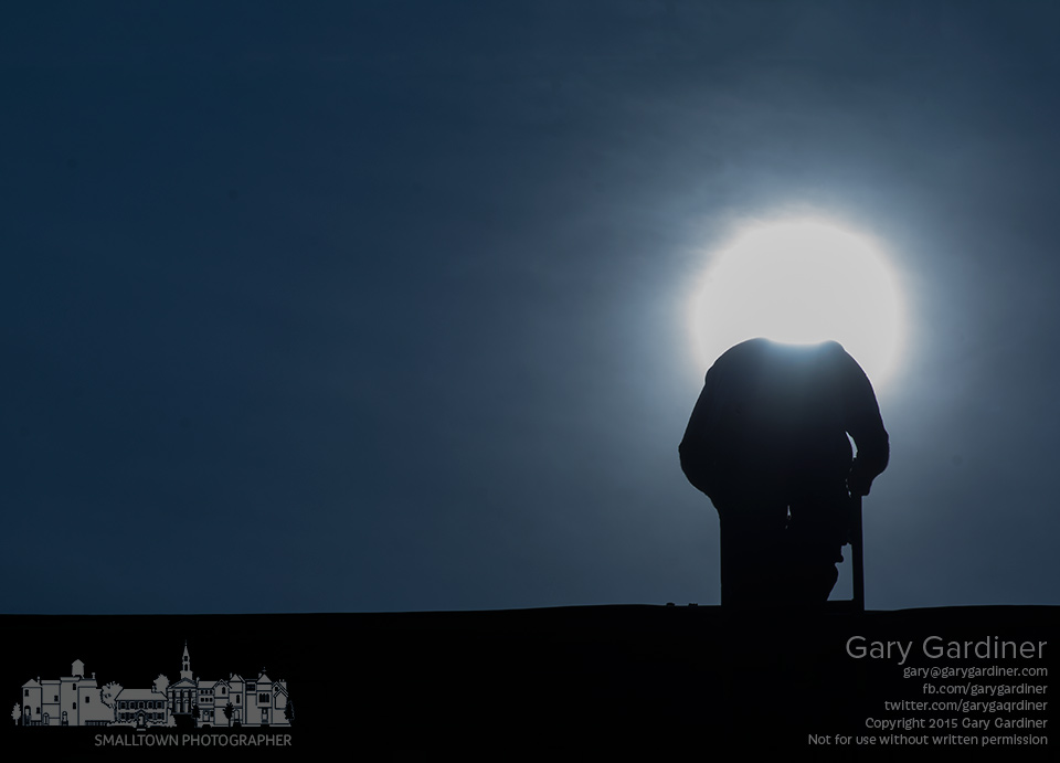 A roofer lowers his head to check the ladder as he leaves the roof where he's been working until near sunset in Uptown Westerville. My Final Photo for Aug. 28, 2015.