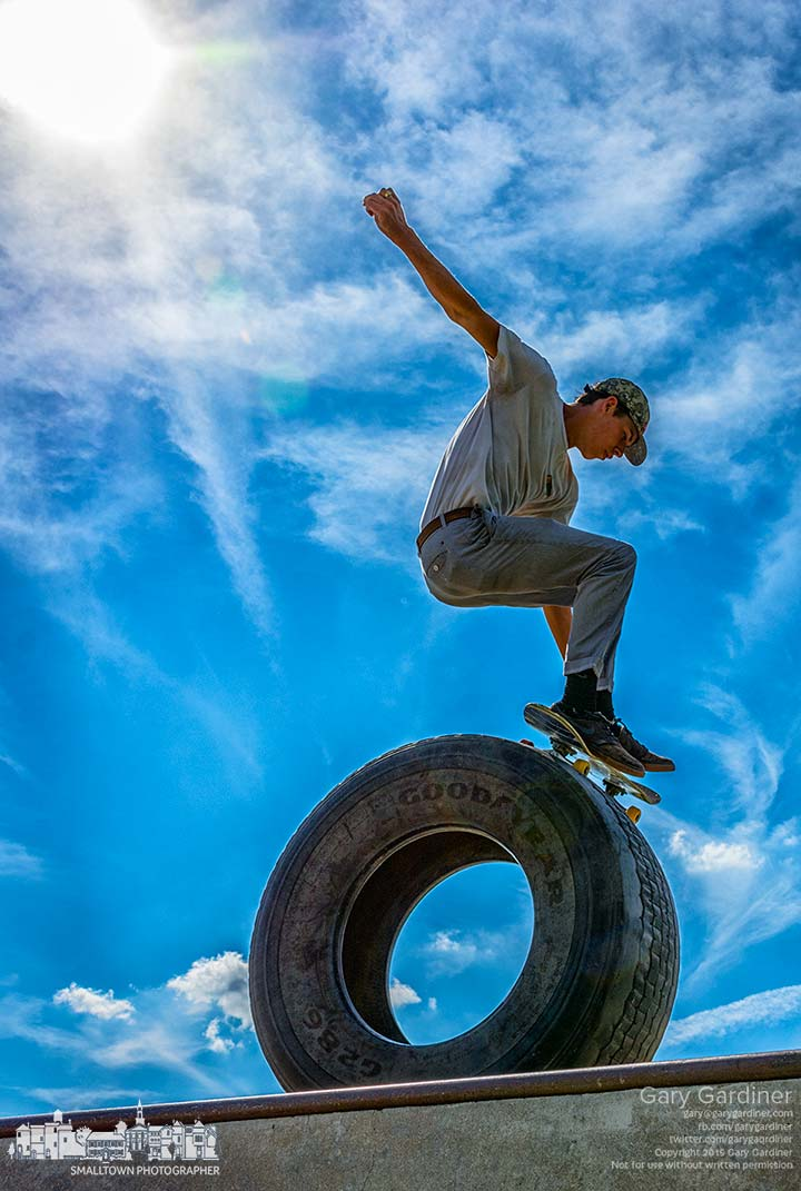 A skateboarder lifts himself over a tire at the edge of a ramp at the Westerville Skatepark on a warm summer afternoon.  My Final Photo for Aug. 4, 2015.