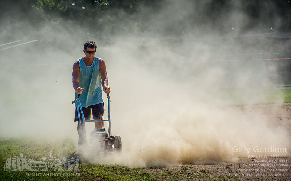 Westerville South baseball coach Tim Bates cuts away weeds and grass growing in the infield during the off season as the field is prepared for the start of fall baseball games. My Final Photo for Aug. 22, 2015.