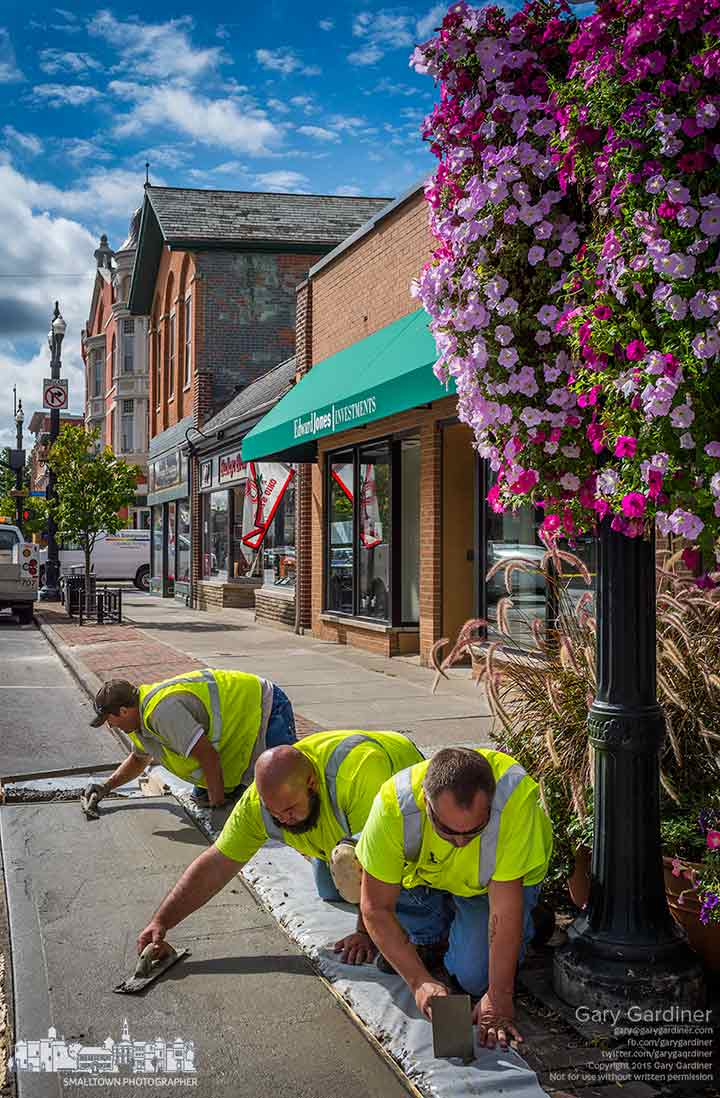 City workers smooth out a section of cement covering half a parking spot in front of the Uptown Deli as part of a project to study Uptown traffic flow, pedestrian traffic, and expanded use of public parking spaces. My Final Photo for Sept. 28, 2015.
