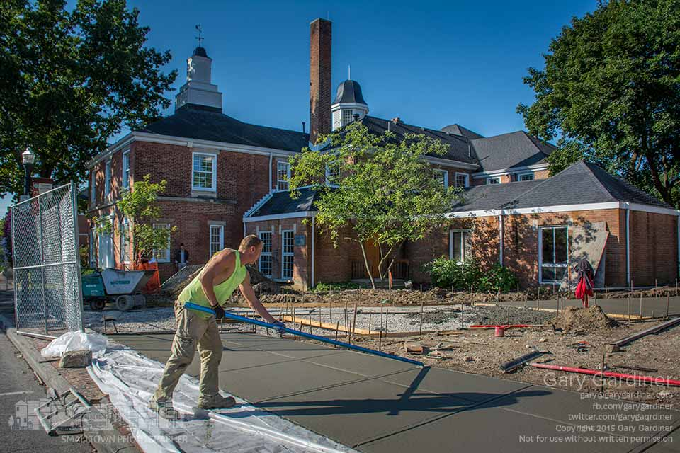 A construction worker puts the finishing touches on a new section of sidewalk at city hall where a brick sidewalk will connect the front of the building with the new expanded and upgraded parking lot. My Final Photo for Sept. 17, 2015.