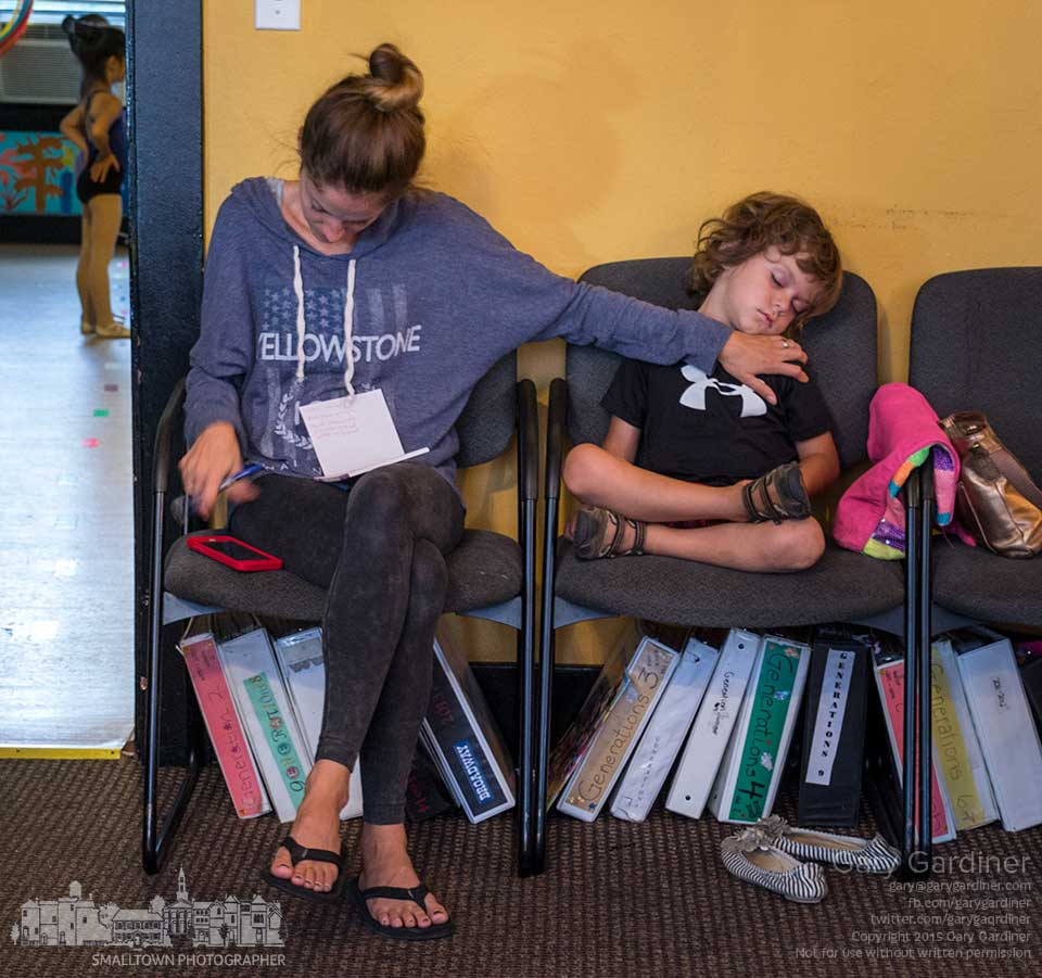A mother uses one arm to steady her sleeping son while using the other to transfer notes from phone to paper as they both wait for another child to finish her performances in Generations PAC dance exhibition during Fourth Friday. My Final Photo for Sept. 25, 2015.