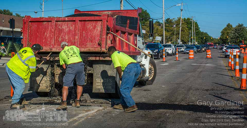 A road crew works quickly to make repairs on Schrock Rd. after heavy traffic forced steel plates off a section of the roadway where contractors recently laid new underground pipes in the first phase of construction to rebuild and expand the intersection with State Street. My Final Photo for Sept. 14, 2015.