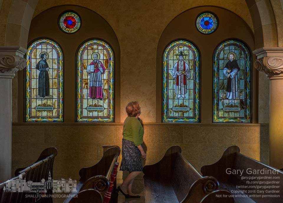 A woman walks through a shaft of colored light cast from an overhead stained glass window as she leaves St. Paul Catholic Church after an early morning Mass. My Final Photo for Sept. 6, 2015.