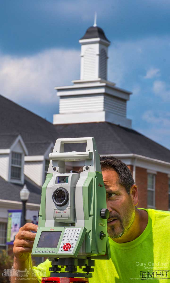 A surveyor measures elevation and distance along the sidewalk along State Street acr4oss from city hall as the city plans road improvements in Uptown Westerville. My Final Photo for Sept. 3, 2015.