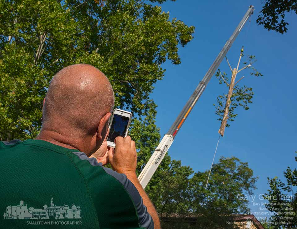 A landscaper uses his cell phone camera for photos of a tree being removed from a clients backyard after it was damaged in a recent wind storm. My Final Photo for Sept. 7, 2015.