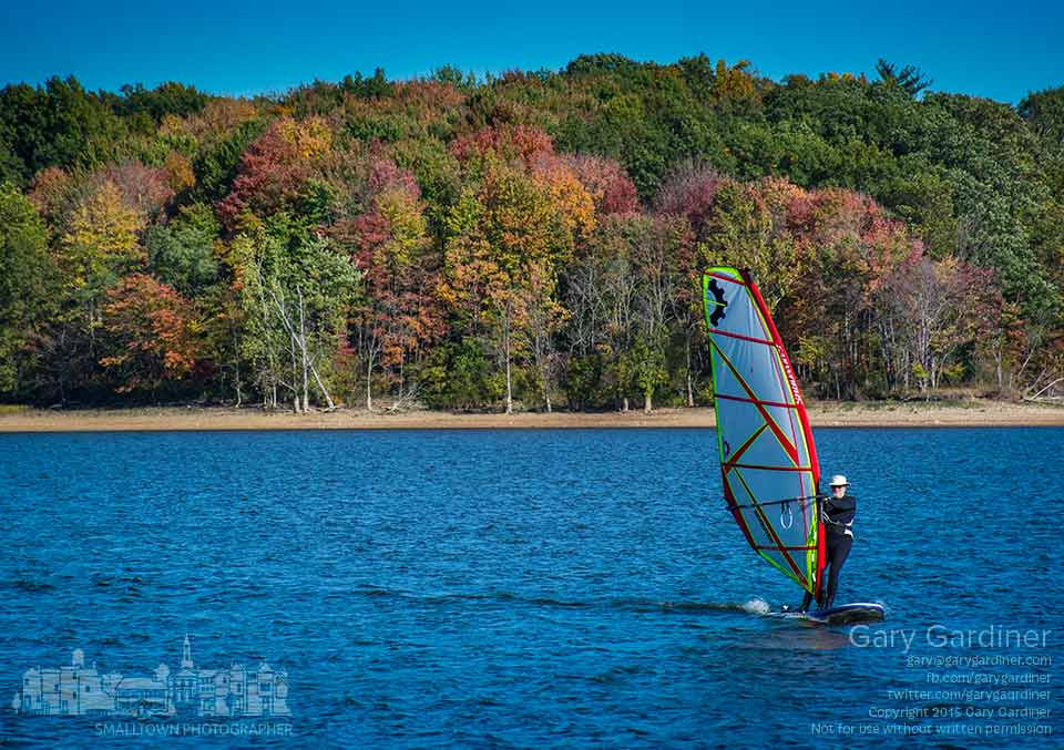 Against a backdrop of colorful fall foliage a sailboarder navigates into the wind crossing Hoover Reservoir on a Sunday afternoon. My Final Photo for Oct. 11, 2015.