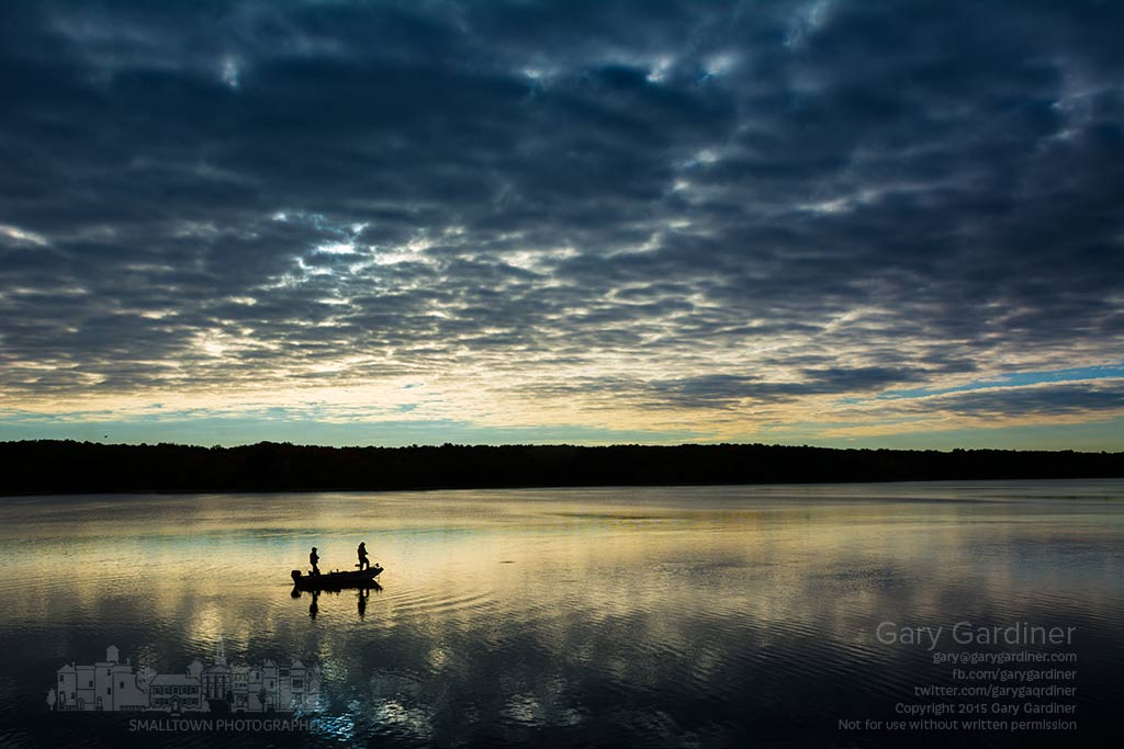 A pair of fishermen slowly troll across the still waters of Hoover Reservoir as the sun tries to break through the heavy morning cloud cover. My Final Photo for Oct. 17, 2015.