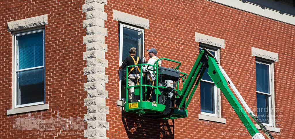 Contractors remove storm windows from the second floor of at the building at College and State where interior windows are being replaced or repaired. My Final Photo for Oct. 20, 2015.