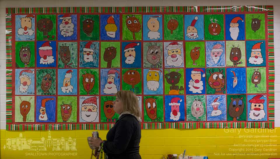 A shopper at the annual Christmas Bazaar fundraiser at St. Paul Catholic church passes under a student created paper art tapestry in the lunchroom while taking a brief break from shopping. My Final Photo for Nov. 22, 2015.