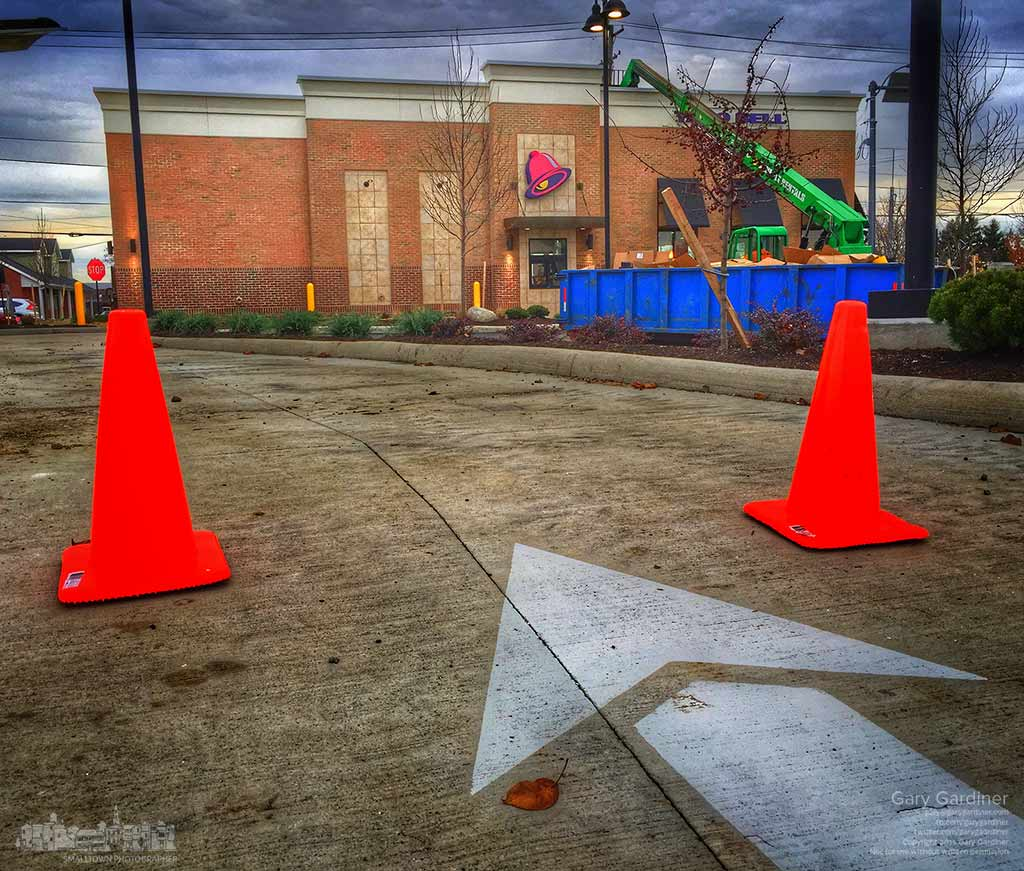Construction cones temporarily block the entrance to the drive thru roadway at the new taco bell as workers complete the installation of seating and kitchen equipment inside the fast food restaurant. My Final Photo for Nov. 17, 2015.