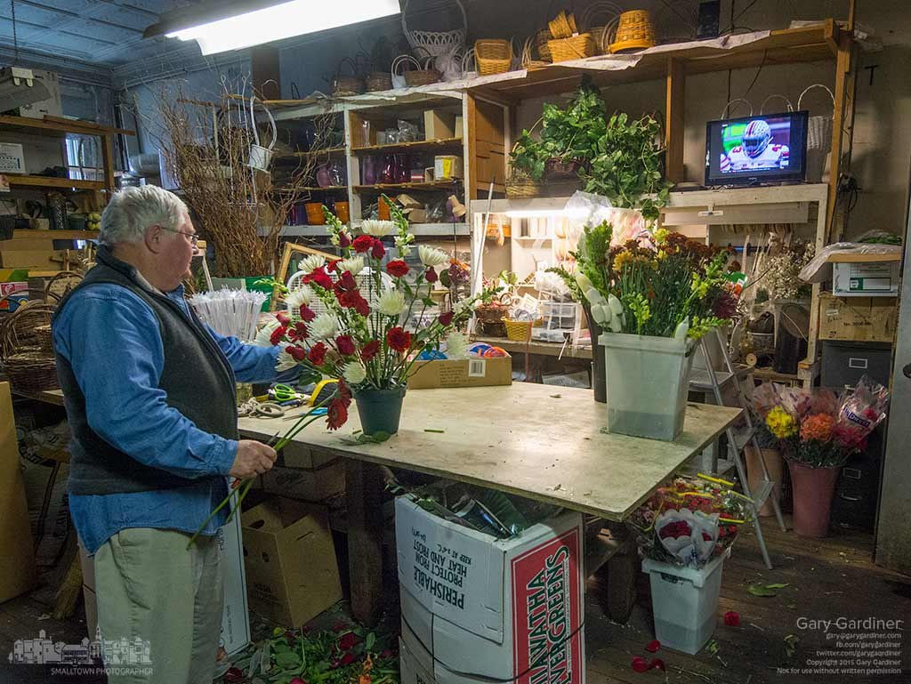 Florist Dave Talbott looks over the bouquet he's creating to watch action from the Ohio State-Michigan football game on the small television in the workroom of his shop in Uptown Westerville. My Final Photo for Nov. 28, 2015.