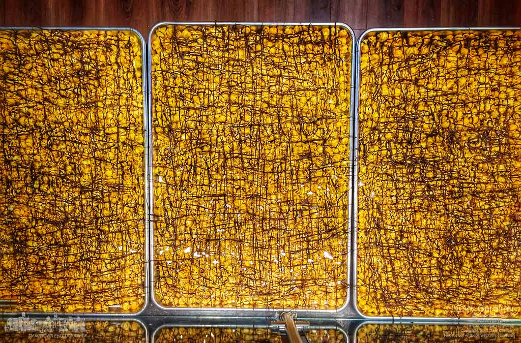 Trays of popcorn drizzled with chocolate sit waiting for a coating of caramel to complete another flavor of popcorn at Shirley's Gourmet popcorn in Uptown. My Final Photo for Dec. 3, 2015.