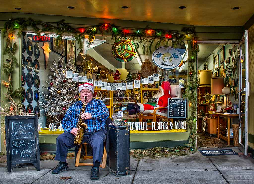 Saxophonist Larry Burgess wears a Santa hat as he plays Christmas music in front of Cinda Lou Shop in Uptown Westerville. My Final Photo for Dec. 23, 2015.