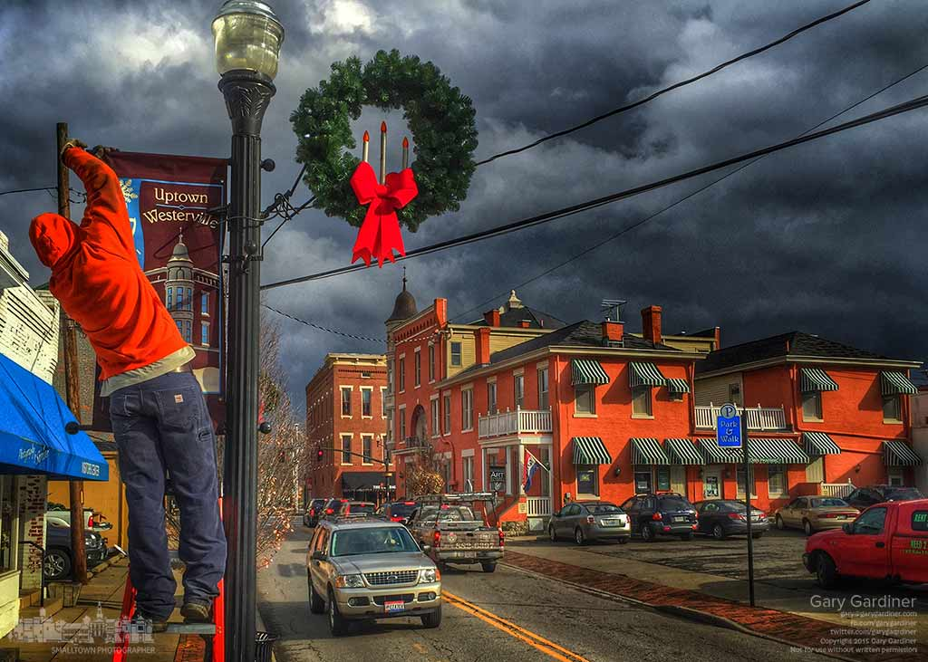 A city worker installs a lighted wreath and seasonal banner on a light pole in West Main Street as crews finished installing holiday decorations through most of the city in preparation for Friday night's tree lighting at city hall. My Final Photo for Dec. 2, 2015.