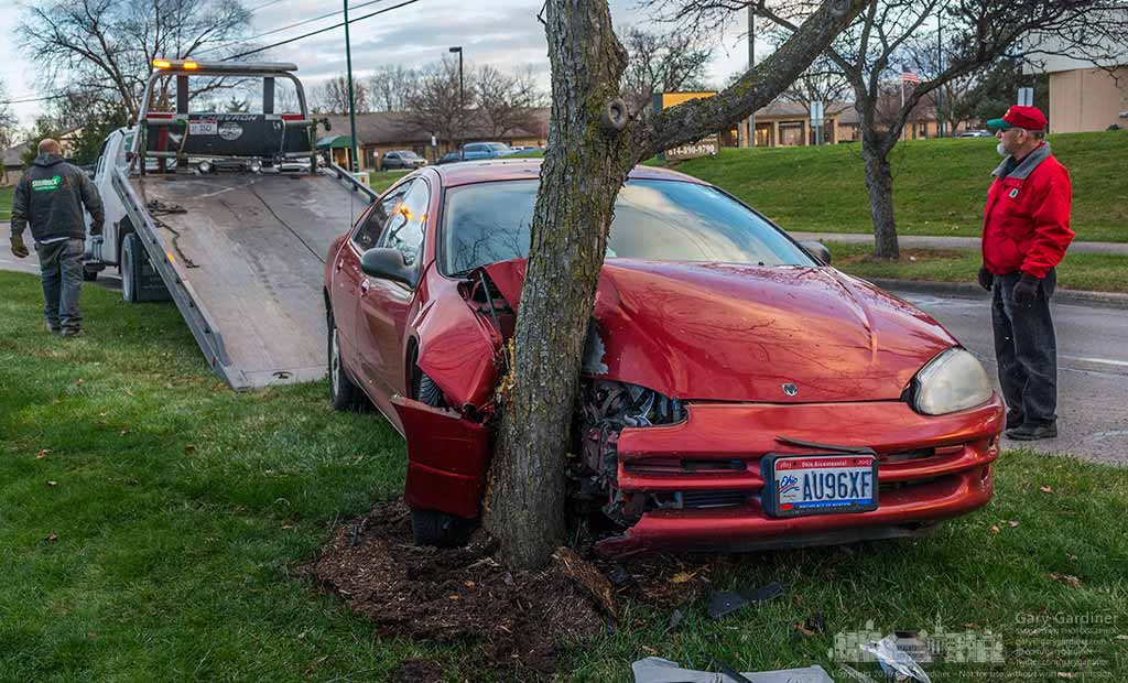 A car's owner watches as a tow truck pulls it away from the tree that became its last stopping place after being struck by another car that failed to yield to crossing traffic on Huber Blvd. My Final Photo for January 3, 2016