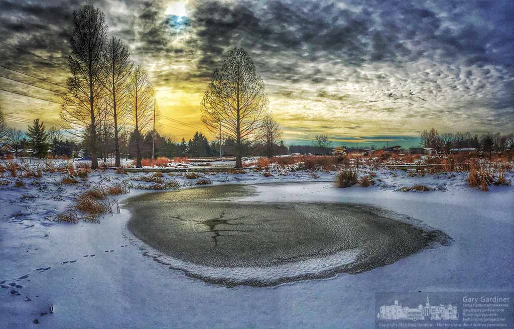 The morning sun breaks through heavy cloud cover at the Highlands Park wetlands where ice slowly envelops the creek that winds through the small park. My Final Photo for January 14, 2016.