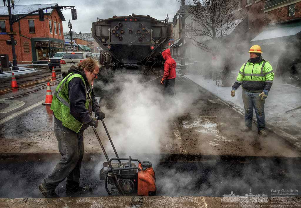 A contractor compacts asphalt covering the trough cut for repair of sewer lines at 18 North State Street in Uptown Westerville. My Final Photo for January 20, 2016.