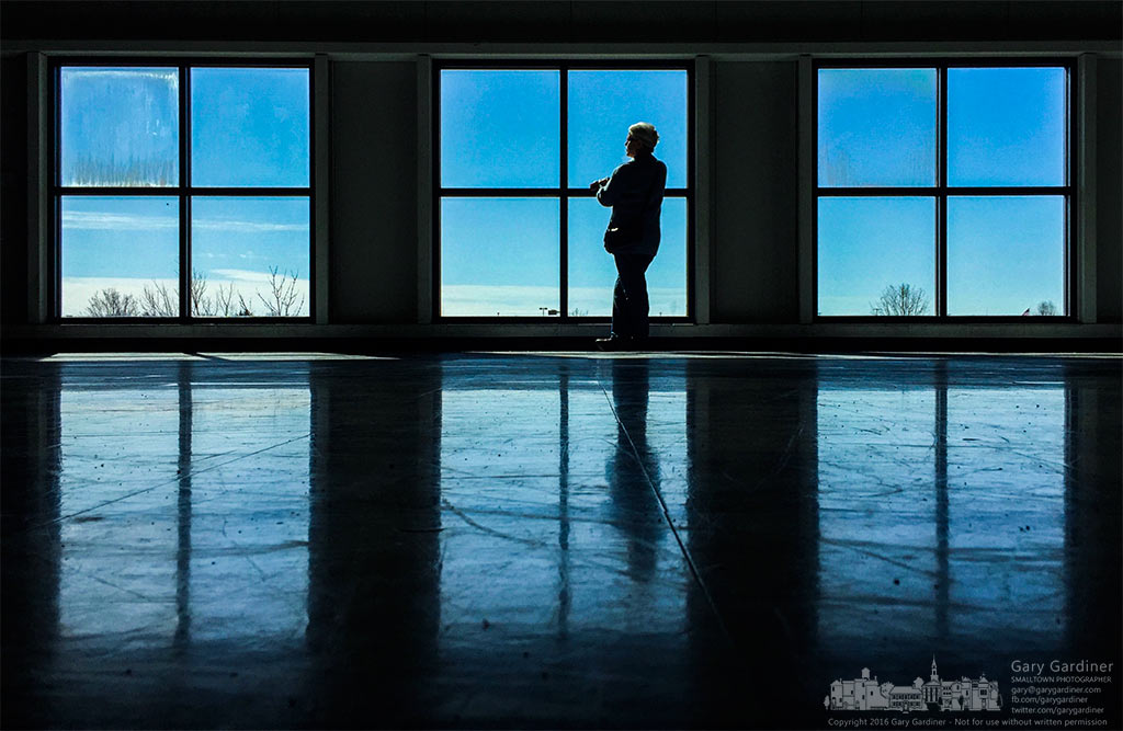 A grandmother stands at the upstairs windows while she waits for her grandsons final hockey match of the regular season to begin. My Final Photo for February 20, 2016.