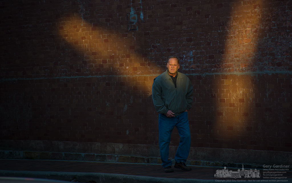 A pedestrian steps through shafts of afternoon sun reflected off a building at State and Main in Uptown Westerville. My Final Photo for February 3, 2016.