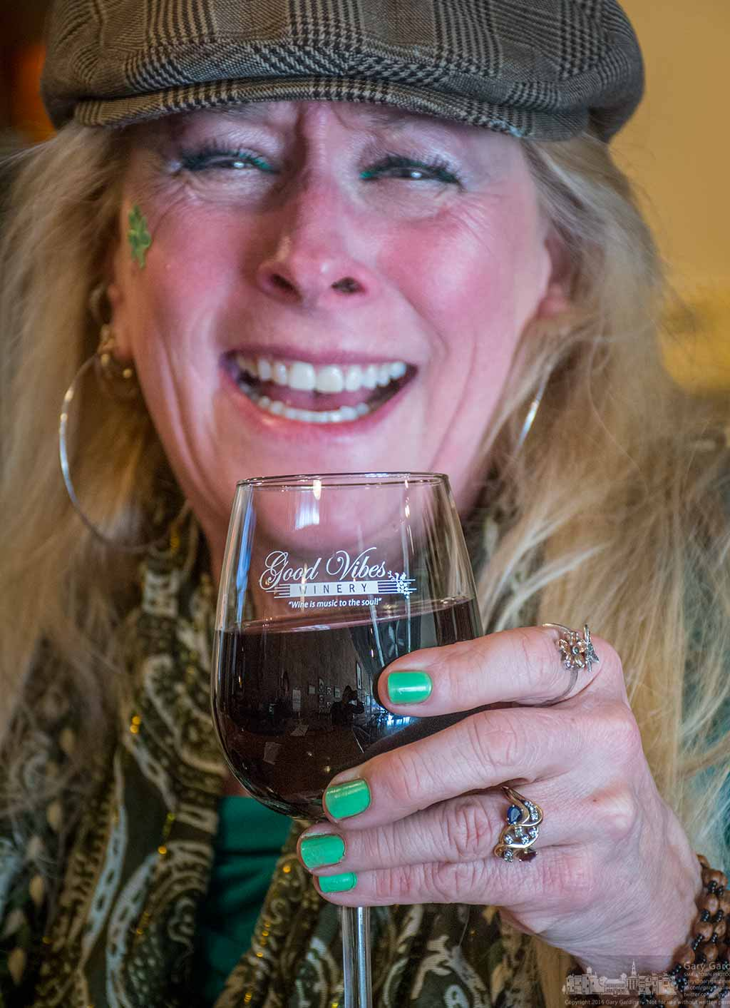 Green fingernail polish, a sticker on the cheek, green eye shadow, appropriately colored clothes, and a hearty laugh help this woman celebrate St. Patrick's Day with a glass of wine at Good Vibes Winery in Uptown Westerville. My Final Photo for March 17, 2016.